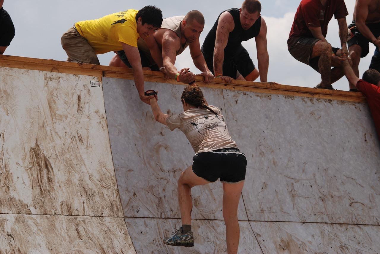 Un gruipo de personas ayudan a una mujer a escalar la última porción de un muro.