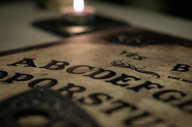 Imagen parcial de un tablero de Ouija con un avela en segundo plano, desenfocada.